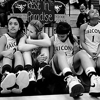 "River Valley High basketball players, from left, Gabby Dagnino, Ashlie Millington, Sara Sandhu, and Aleqse Hawkins, sit next to the bleachers as Jordan Mahon performs his song, ""Can't Back Down"" during half-time at the first Kayla Lizama-Pierson Dedication Game in Yuba City on Friday, January 11, 2013. (Nate Chute/Appeal-Democrat)"
