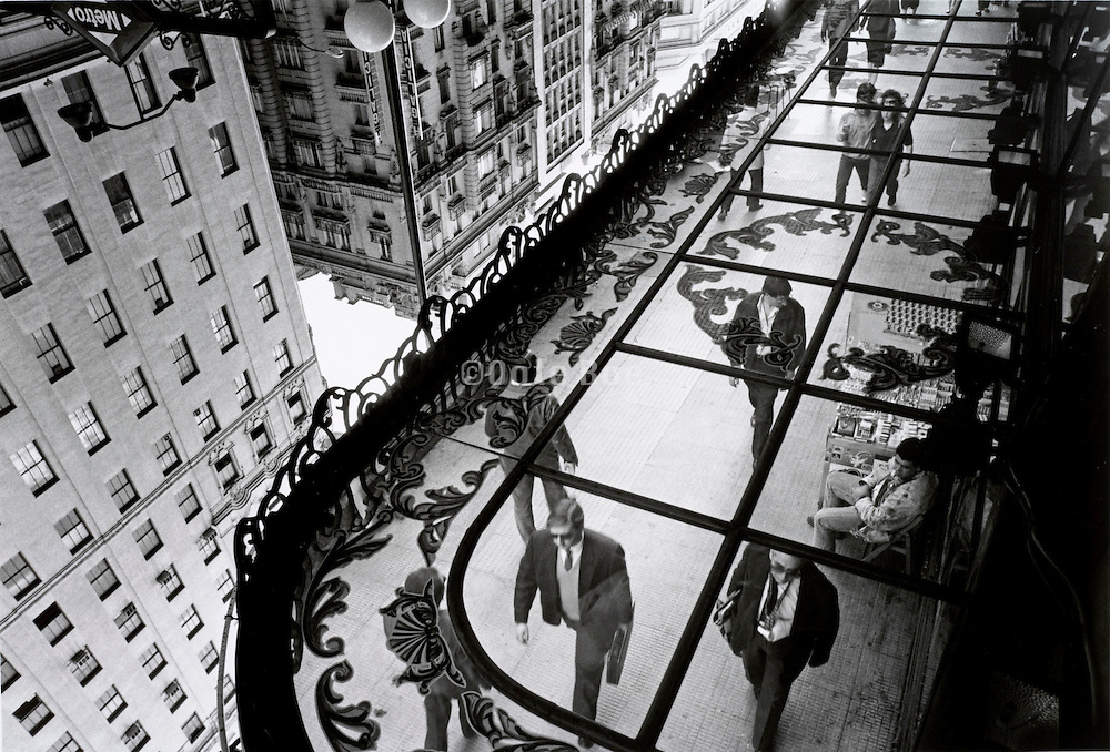Street scene with people walking reflected in mirrored roof Madrid, Gran Via