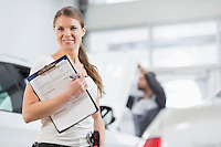 Portrait of smiling female repair worker with clipboard in car workshop