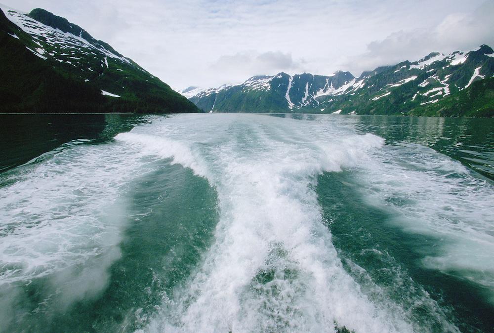 Large wake of boat in the water of Holgate Arm Fjord off Kenai Peninsula Alaska USA