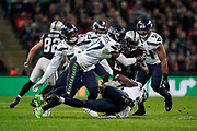 Oakland Raiders Running Back Mershawn Lynch (24) is tackled by Seattle Seahawks Linebacker Barkevious Mingo (51) and Seattle Seahawks Defensive Back Tre Flowers (37) during the International Series match between Oakland Raiders and Seattle Seahawks at Wembley Stadium, London, England on 14 October 2018.