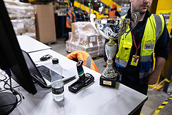 """© Licensed to London News Pictures . 04/12/2019. Manchester , UK . MAN1 Inbound Cup Winner trophy awarded to the team who most efficiently processed incoming stock in a quarter-year period . Inside the """"MAN1"""" Amazon fulfilment centre warehouse at Manchester Airport in the North West of England . Photo credit : Joel Goodman/LNP"""