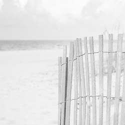 Black and white panorama photo of a beach fence on Casino Beach in Pensacola Beach Florida. Pensacola Beach is a coastal city in the Emerald Coast area of the Southeastern United States. Copyright ⓒ 2018 Paul Velgos with All Rights Reserved.
