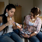 London, UK, December 2011. .Teenage Parents Service at the South London YMCA charity in Lambeth..Carolina with her friend Fernanda and her son Jayden. Carolina, 17 years old from Colombia, got pregnant when she was 16. At that time she was really worried to face her parents and about not being able to cope with the baby. When she had the baby she went to live at Teenage Parents Service residence for teenage mothers in Stockwell.