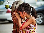 21 NOVEMBER 2015 - BANGKOK, THAILAND: A girl and her grandmother pray at the Wat Saket temple fair. Wat Saket is on a man-made hill in the historic section of Bangkok. The temple has golden spire that is 260 feet high which was the highest point in Bangkok for more than 100 years. The temple construction began in the 1800s in the reign of King Rama III and was completed in the reign of King Rama IV. The annual temple fair is held on the 12th lunar month, for nine days around the November full moon. During the fair a red cloth (reminiscent of a monk's robe) is placed around the Golden Mount while the temple grounds hosts Thai traditional theatre, food stalls and traditional shows.     PHOTO BY JACK KURTZ
