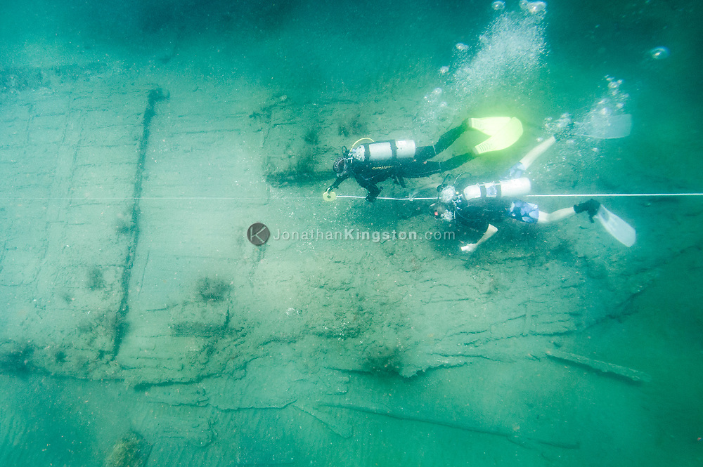 Archaeologists Christopher Horrell and Vicente Cortez take a baseline measurement of the Encarnación, a 17th century shipwreck discovered during an expedition looking for Henry Morgan's lost fleet of 1671 in Panama.