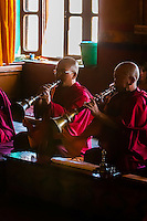 Buddhist monks of the Yellow Hat sect blow horns at the Diskit Monastery, Nubra Valley, Ladakh, Jammu and Kashmir State, India.