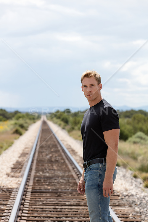 handsome man standing by a railroad track
