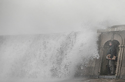 © Licensed to London News Pictures. 03/03/2019. Lyme Regis, UK. A visitor to Lyme Regis in Dorset hides from waves whipped up by storm Freya. Photo credit: Jason Bryant/LNP