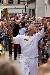 © Licensed to London News Pictures. 19/05/2012. Truro, UK. An Olympic torchbearer carries the Olympic flame through Truro, Cornwall as part of the 70 day relay across the UK. Photo credit : Ashley Hugo/LNP