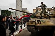 Tunisi, Africa, 20 gennaio 2011. Un manifestante cerca di salire su un carro armato dell'esercito tunisino durante una manifestazione contro il neo-governo tunisino che si è appena insediato dopo la caduta del presidente Zine el Abidine Ben Ali e del suo partito RCD. L'esercito continua a predidiare le strade con carri armati e mezzi blindati e il coprifuoco è ancora in vigore..Ph. Roberto Salomone Ag. Controluce.AFRICA - A protestors tries to climb on a tunisian army tank during a rally against the new tunisian government in Tunis on January 20, 2011. Tunisian army continues to patrol the streets of Tunis with tanks and the curfew is still on going.