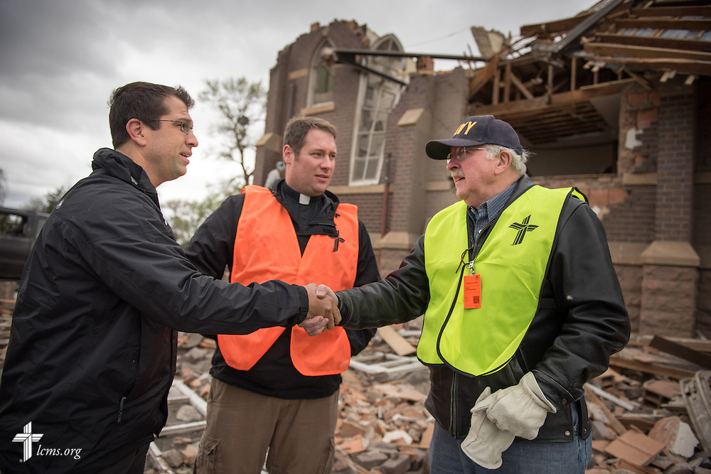 (L-R) The Rev. Ross Johnson, director of LCMS Disaster Response, the Rev. Michael Meyer, manager of LCMS Disaster Response, and the retiring South Dakota District President Rev. Dr. Dale Sattgast, shake hands amongst the rubble of Zion Lutheran Church on Monday, May 11, 2015, in Delmont, S.D. A tornado swept through the area the previous day and destroyed the church and nearby buildings. LCMS Communications/Erik M. Lunsford