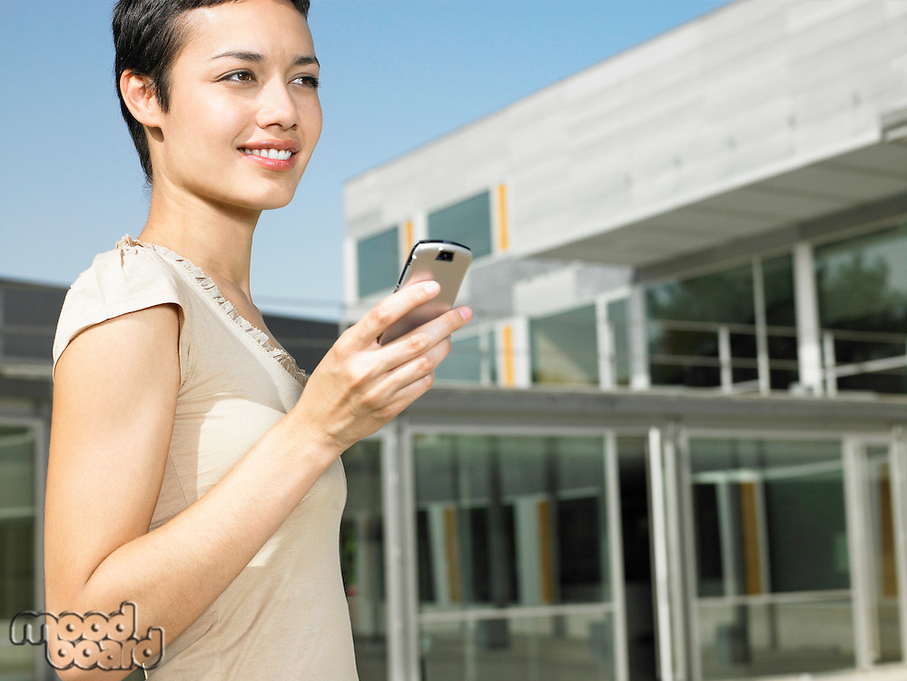 Smiling young woman standing in plaza sending text message
