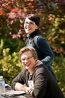Two students on the North Island College campus share lunch outside.  Comox, The Comox Valley, Vancouver Island, British Columbia, Canada.
