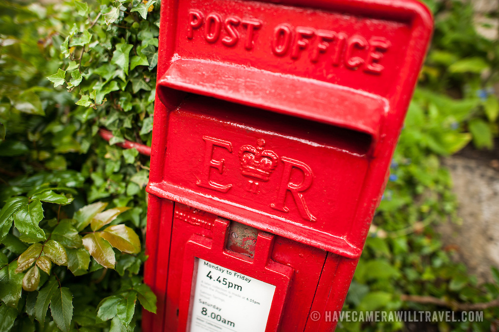 Bright red royal post box in Painswick, England.