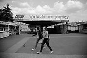 Two teenage girls passing the main train station. Bielsko Biala, Silesia, Poland. April 2009.