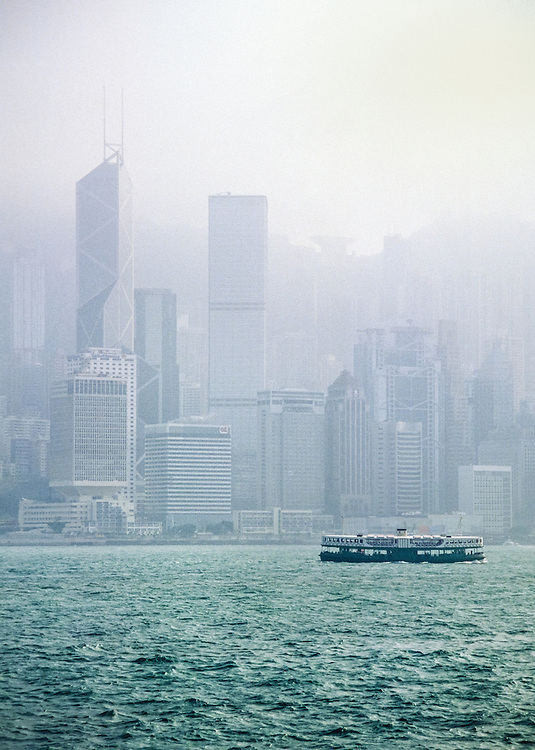 The Star Ferry crosses Victoria Harbour from Tsim Sha Tsui (Kowloon) to Hong Kong Island. To the left is the Bank of China tower, and in the background Victoria Peak is hidden behind a thick cloud of fog. Hong Kong, 2001.