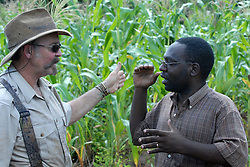Lion researcher Dennis Ikanda talks to trapper Dairen Simpson in a village near Simana,  outside of Lindi, Tanzania.