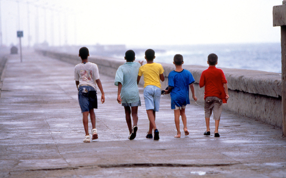 Boys in colorful shirts walk the long boardwalk in Havana Cuba in the afternoon