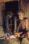 Indonesian headman with ancestral mummy, Pummo Village, Irian Jaya, Indonesia. (Man Eating Bugs page 13).
