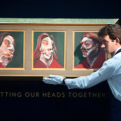 """London,UK - 7 June 2013: A Sotheby's employee named Chris looks up at a work by Francis Bacon entitled """"Three studies of Isabel Rawsthorne, 1966"""" (Est. £10-15 million) during the preview of this summer auction estimated at £100 million."""