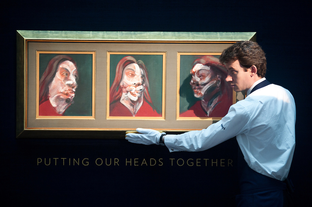 "London,UK - 7 June 2013: A Sotheby's employee named Chris looks up at a work by Francis Bacon entitled ""Three studies of Isabel Rawsthorne, 1966"" (Est. £10-15 million) during the preview of this summer auction estimated at £100 million."
