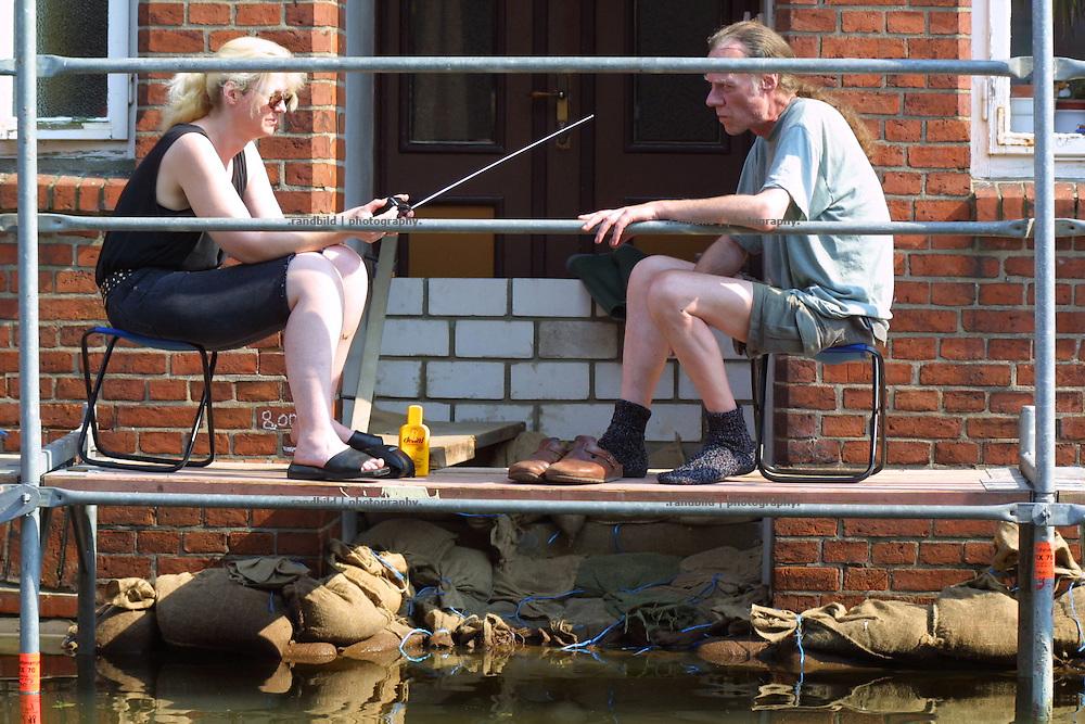 Elbe floods in Hitzacker. Zwei Einwohner Hitzackers sitzen vor ihrer zugemauerten Haustür und warten mit Radio und Sonnencreme darauf, dass das Hochwasser der Elbe sich wieder aus der Stadt zurückzieht.