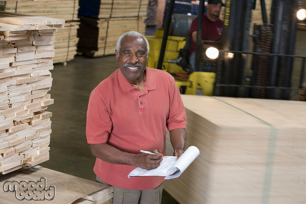 Senior man stock-taking in warehouse