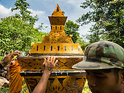 20 JUNE 2016 - DON KHONE, CHAMPASAK, LAOS: Men move the coffin into place before the cremation of a man from Don Khone village on Don Khone Island. Don Khone Island, one of the larger islands in the 4,000 Islands chain on the Mekong River in southern Laos. The island has become a backpacker hot spot, there are lots of guest houses and small restaurants on the north end of the island. In the southern Lao funeral tradition, the deceased is cremated at the place of his choosing, usually a place he (or she) was especially fond of. In this case, the man chose to be cremated in a small clearing in the jungle a few kilometers from his home.     PHOTO BY JACK KURTZ