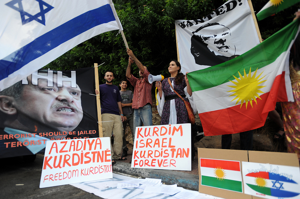 Israelis hold up placards, including a portrait of Turkey's Prime Minister Recep Tayyip Erdogan' labeled wanted, during an anti-Turkish protest outside the Turkish embassy in Tel Aviv on July 08, 2010. Protesters waved Kurd flags and chanted slogans in favor of the Kurd people and against, what they call, their depression by Turkey. Photo by Gili Yaari