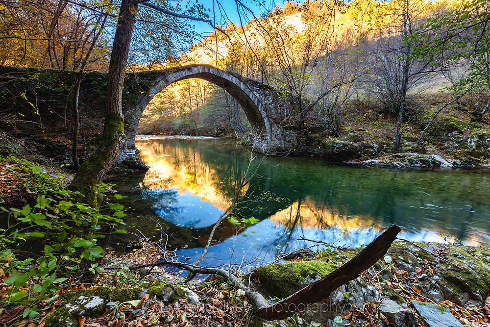 Old stone bridge above a river in the forest