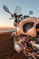 A 1960s BMW R60US motorcycle (PR) on the side of a coastal road in Sonoma County California, at sunset.