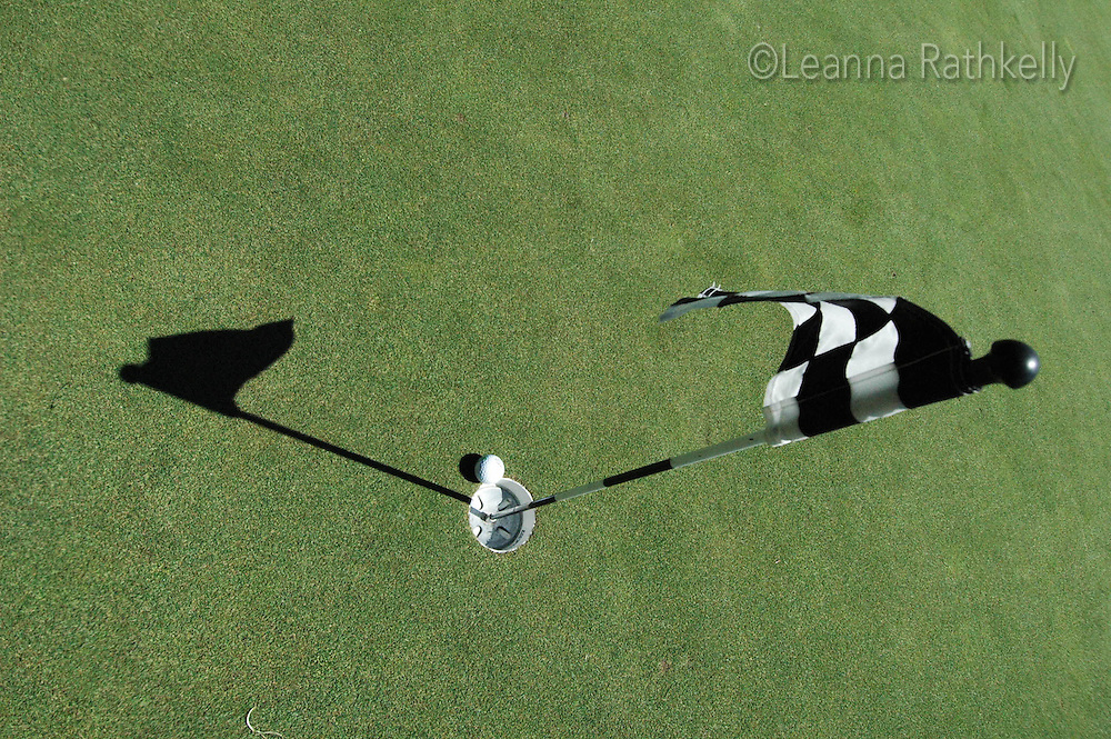 A golf ball nears the hole as seen from above.