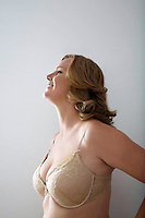 Woman in bra smiling against gray background