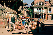 Man carrying heavy pots on shoulder hoist, Patan, Nepal