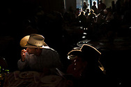 Jason Mossy of Rancho Santa Fe, California, licks his fingers while finishing a chuck wagon-themed meal with his wife Melisse and daughter Savannah Jane during a cowboy poetry gathering at the Village Community Presbyterian Church in Rancho Santa Fe on October 11, 2009.