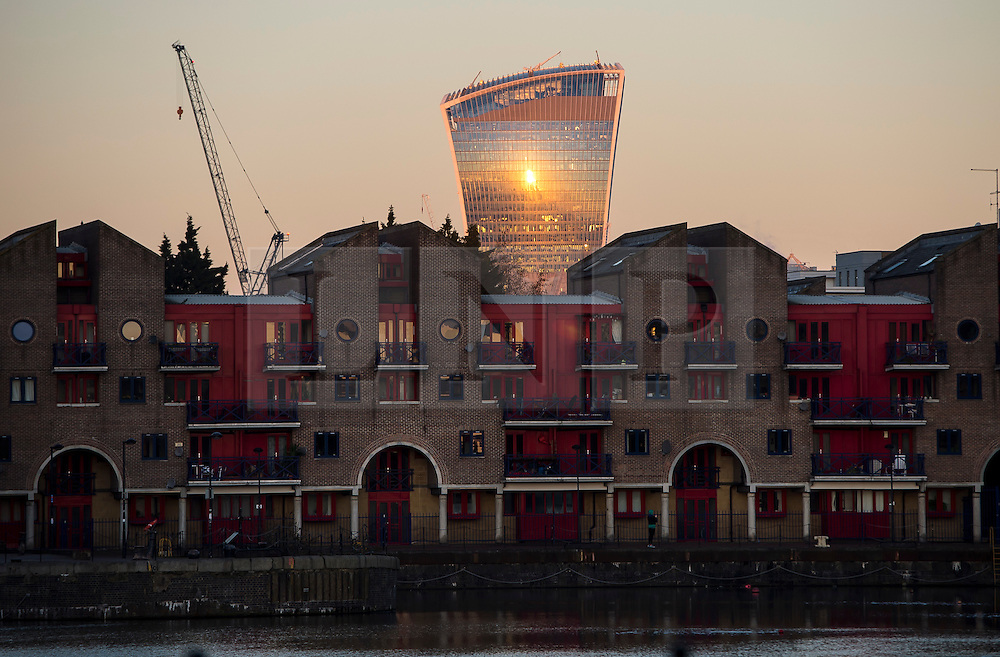 """© Licensed to London News Pictures. 07/03/2016. London, UK. The Sun reflected off 20 Fenchurch Street, also known as the """"walkie talkie building' behind residential housing, at sunrise in London on a clear morning on March 07, 2016. Photo credit: Ben Cawthra/LNP"""
