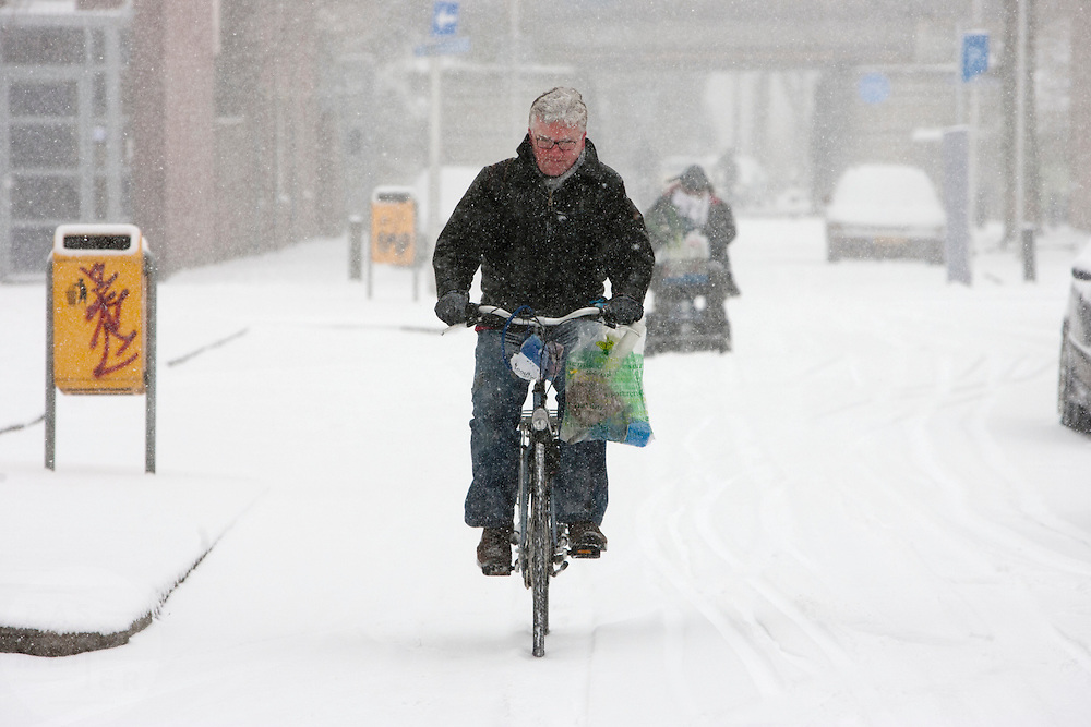 Een fietser rijdt door de sneeuw. <br /> <br /> A cyclist is riding in the snow