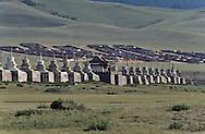 Mongolia. monastery Karakorum  Erden Zuu      /  Deux stupas d'angle de la muraille de ERDENI ZUU QARAQORIN (XVIèmesiècle). Les stupas ou suburgan sont des sortes de sépulture pour la conservation des reliques de  - Saints Lamas -  ou prêtres de distinction, qui ont été ou bien incinérés ou bien momifiés par le sel et le mercure, selon une technique complexe. Le corps du défunt était ensuite ceint de bandelettes sur lesquelles on appliquait un mélange de cendre et d'argile. Le tout était recouvert d'or ou d'argent. /  Erigés selon le style tibétain, ils sont composés en trois parties : un piédestal, un châsse et une flèche de treize anneaux qui symbolisent les treize cieux. Au sommet, couronnant le tout, l'emblème cosmique qui regroupe croissant de lune, soleil et flamme de la sagesse. A chaque angle de la muraille aux stupas encastrés du monastère de ERDENI ZUU, on peut ainsi trouver, l'un derrière l'autre, deux stupas isolés .Devant le premier, un monticule de pierres ou oboo témoigne d'une forme encore vivante de religion populaire d'essence chamanique, antérieure au lamaïsme. ( /  /29    L920728a  /  P0002634