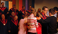 "23 Oct. 2011 -- ST. LOUIS -- Katie Hotze-Wilton (right), director of media and worship at the Metropolitan Community Church of Greater St. Louis, leads members of the congregation in laying hand on and praying for the church's senior pastor the Rev. Dr. Carol Trissell (in red) and music director Jerry Smith to support the church's choir during Sunday morning services at the church in St. Louis Sunday, Oct. 23, 2011. The choir recently qualified to represent the St. Louis region at the national gospel choir competition ""How Sweet The Sound"" at the Staples Center in Los Angeles Oct. 28. Photo © copyright 2011 Sid Hastings."