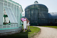 A few months a year the Royal greenhouses in Laken, Brussels, Belgium, are open to the public. These two visitors bend over to see the flowers inside. two kids looking inside