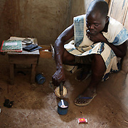 A gold buyer is burning off the mercury used to extract the gold from the muddy water. He will then weigh the gold and pay around $28/gr. The mines in the small community near Bolgatange in Northern Ghana are dug with shovels and spades and held up by timber, all very precarious. The mine shafts go deep into the ground and run along under the surrounding fields. The small community which has sprung up around the gold finds consists of poor people from all over Northern Ghana,most of them now stuck, not making much money and in dept to their gold dealers.