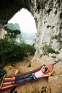 Li Shengiang finds the ultimate nap spot at Moon Hill near Yangshuo, China. (model released)