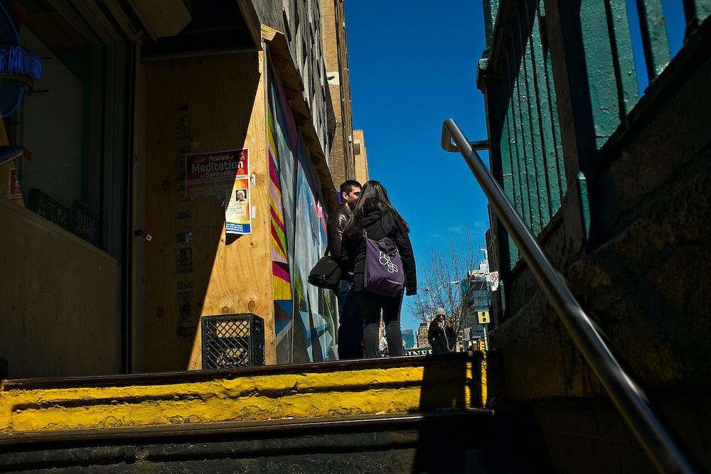 Man and woman talking near subway entrance, New York, NY, US