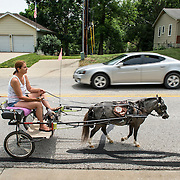 "Lori McDermott of Shawnee led ""Cody,"" a Class A miniature horse, on a westbound walk in Shawnee on 67th Street near Mullen on Friday afternoon as one of Cody's three weekly walks. Cody, a therapy horse in training who visits nursing homes, gets exercise and desensitized to loud noises during the walks on city streets."