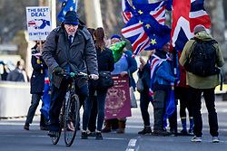 """© Licensed to London News Pictures. 11/03/2019. London, UK. Former Foreign Secretary Boris Johnson MP (L) cycles through a group of anti-Brexit protesters as he heads to Parliament. MPs will get a second """"meaningful vote"""" on Prime Minister Theresa May's proposed Brexit deal tomorrow. Photo credit: Rob Pinney/LNP"""