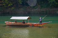 A boatman taking tourists sightseeing on the Oi River, Arashimaya, Kyoto, Japan