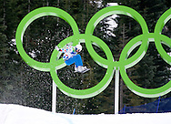 A snowboarder gets some air while competing in the Snowboard Cross event at Cypress Mountain.