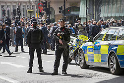 © Licensed to London News Pictures. 10/04/2017. London, UK. Armed police officers guard the route as the funeral cortege carrying the coffin of policeman Keith Palmer leaves from Southwark after a service was held at the cathedral. PC Palmer was murdered just inside the main gates of Parliament by Westminster attacker Khalid Masood - an attack in which he also killed four people on Westminster Bridge. PC Palmer's funeral will take place at Southwark Cathedral today. Photo credit: Peter Macdiarmid/LNP