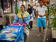 06 JULY 2011 - BANGKOK, THAILAND: A snack vendor pushed her cart through the Soi Arab neighborhood in Bangkok. Soi Arab is an alleyway in Bangkok. What started as an alley has now grown into a neighborhood that encompasses several blocks of restaurants, hotels and money exchanges that cater to Middle Eastern visitors to Thailand. The official name of the street is Sukhumvit Soi 3/1, located in North Nana between Sukhumvit Soi 3 and Sukhumvit Soi 5, not far from the Nana Plaza night-life area and the Grace Hotel popular among Arabs.   PHOTO BY JACK KURTZ